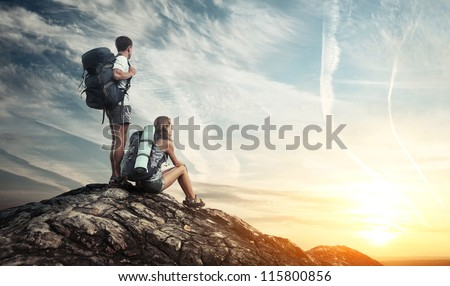 Two tourists with backpacks enjoying sunset on top of a mountain