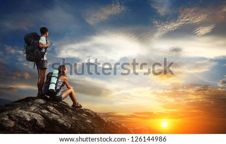 Two tourists with backpacks relaxing on top of a mountain and enjoying sunset view
