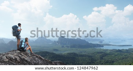 Two tourists with backpacks relaxing on top of a mountain and enjoying valley view - stock photo