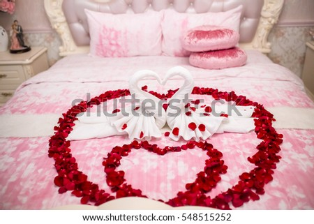 two towel swans shaped on the bed,Honey moon bed.Honeymoon, Wedding bed topped with rose petals.