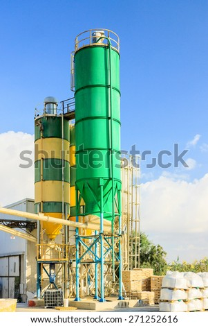 Two towers on chemical plant, big green and orange cisterns - stock photo