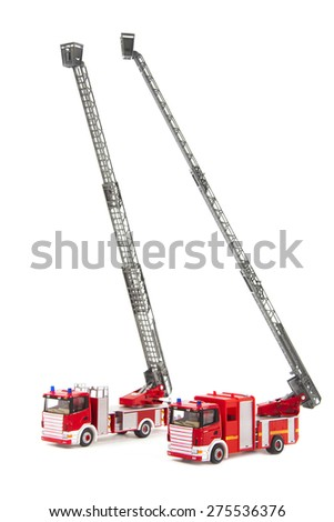 two toy firetrucks wit ladders extended are isolated on white background  - stock photo