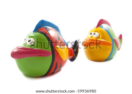 Two toy fishes in different colors isolated over white - stock photo