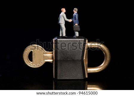 Two toy model miniature businessmen shake hands standing on top of a padlock and key, conceptual od business security - stock photo