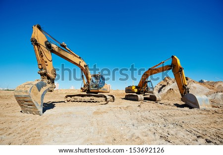 Two track-type loader excavator machine at earthmoving work in sand quarry - stock photo