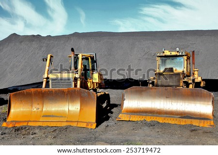 two tractor on the background of coal in Donetsk - stock photo