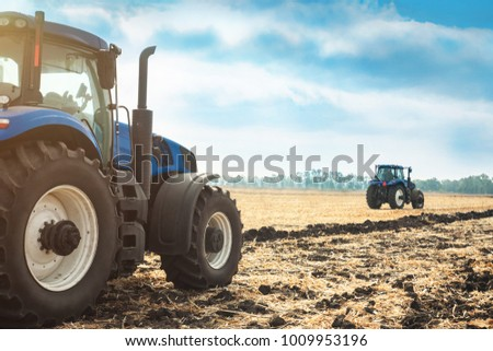 Two tractors working in a field on a sunny day. Agricultural machinery during planting.