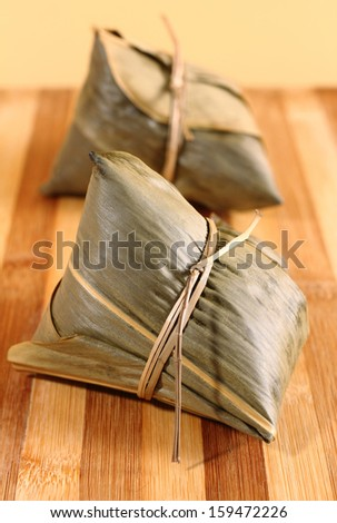 Two traditional homemade chinese rice dumplings on yellow wooden background