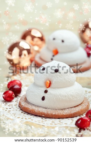 Two traditional marshmallow snowmen biscuits with Christmas decorations, closeup shot - stock photo
