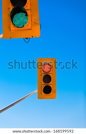 Two traffic lights, green and red, confusing and contradicting against blue sky with copyspace - stock photo