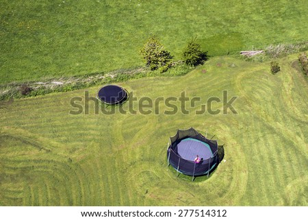 Two trampolines on green grass seen from above - stock photo