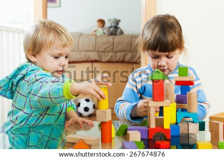 Two tranquil children playing with wooden blocks  in home interior - stock photo