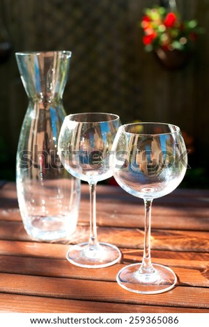 Two transparent shiny empty wineglasses and carafe in rays of sunlight on wooden table. Summertime outdoors.