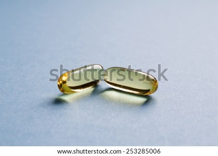 Two transparent yellow capsules on blue table. - stock photo