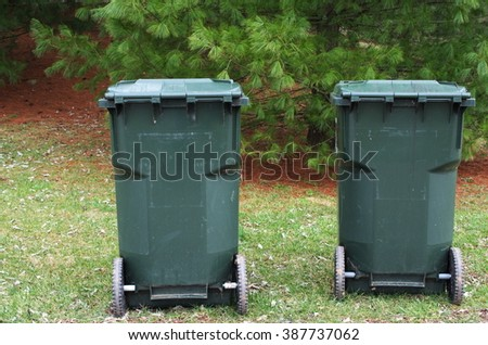 Two trash bins on wheels are on the green grass against a backdrop of trees waiting for a neighborhood garbage truck to collect the waste. - stock photo