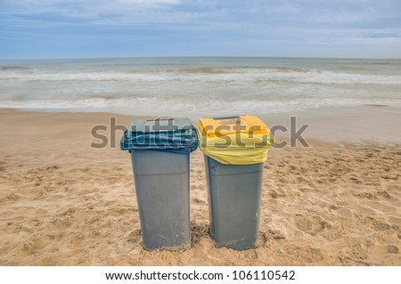 Two trash cans on the beach with a cloudy day - stock photo