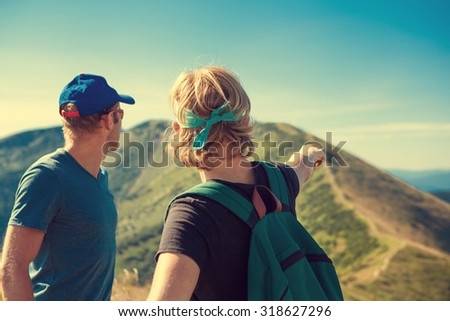 Two travelers discuss itinerary on the top of mountain hill - stock photo