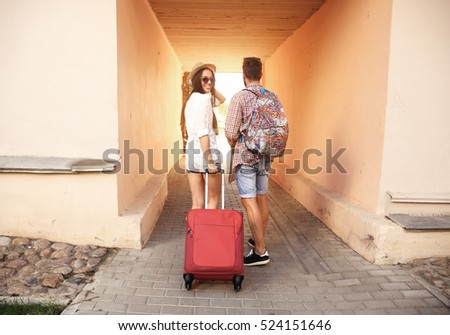 Two travelers on vacation walking around the city with luggage