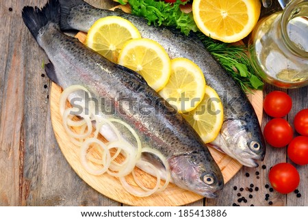 two trout on a cutting board with vegetables  - stock photo