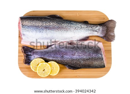 Two trouts on wooden plate isolated on white background - stock photo