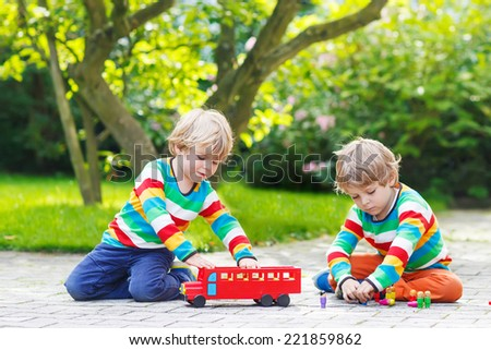 Two twin boys in colorful clothing with stripes playing with red school bus and toys in summer garden on warm sunny day. Learning to play and communicate together. - stock photo