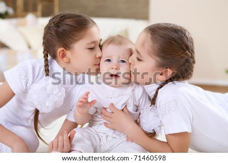 two twin sisters at home together with baby