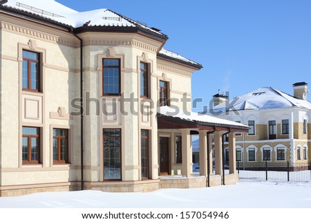 Two two-storey new cottages with big windows on sunny frosty winter day. - stock photo