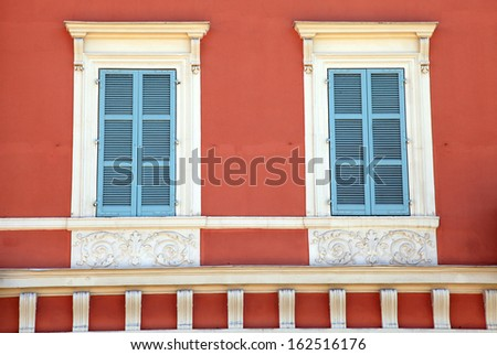 two typical old french blue shutter windows in red house of Nice, Cote d'azur, France.  - stock photo