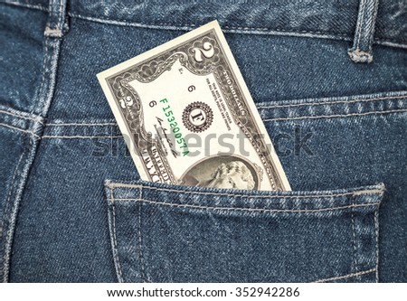 Two U. S. dollars bill sticking out of the back jeans pocket