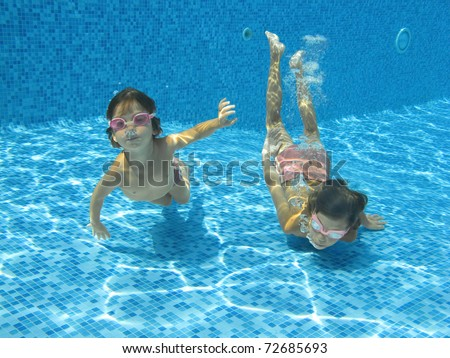 Two underwater girls in swimming pool - stock photo