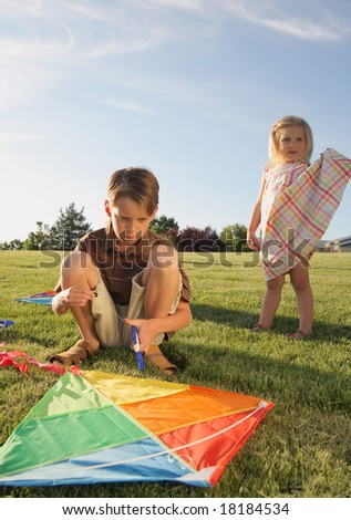 Two unhappy children outdoors with a kite