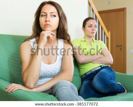 Two unhappy young girls having conflict at home - stock photo