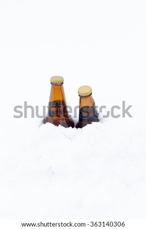 Two unopened bottles of beer covered to the neck in freshly fallen snow - stock photo