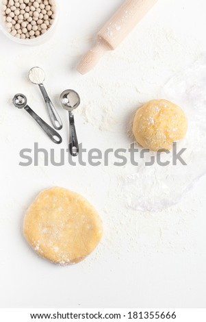 Two unrolled and unbaked shortcrust pastry dough with assorted baking tools: three measuring spoons, rolling pin and ceramic baking beans. Taken on a floured white surface, directly from above. - stock photo