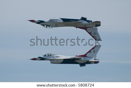 Two US Air Force Thunderbirds, one flying inverted - stock photo