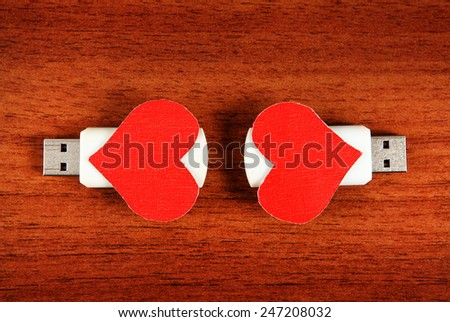 Two USB Flash Drive with Heart Shapes on the Wooden Background - stock photo