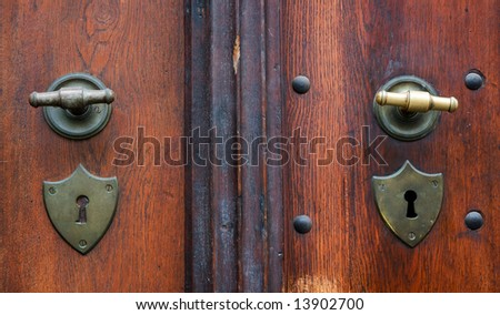 Two used handles and keyholes at wooden door