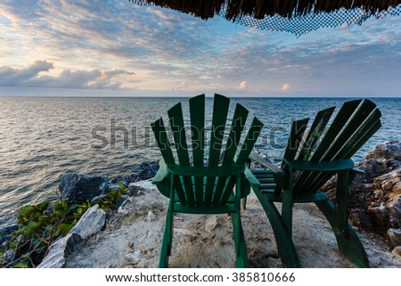 Two vacant green chairs await visitors to relax and enjoy sunset from isolated rocky point in Caribbean sea - stock photo