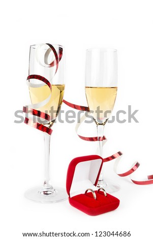 Two Valentine's champagne glasses with jewelery on white background