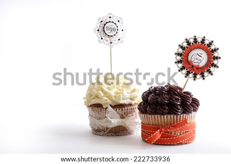 Two vanilla cupcakes with chocolate and lemon frosting decorated for Halloween.  - stock photo