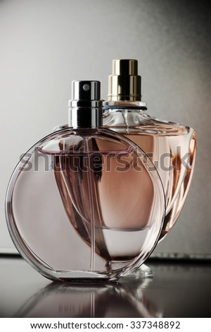Two various bottles of woman perfume on dark gray background. Toned image.