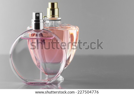 Two various bottles of woman perfume on gray background. - stock photo