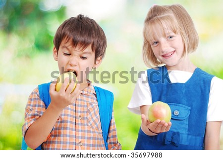 Two very cute children eating fruits outdoor - stock photo