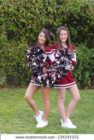 Two very cute teen aged cheerleaders posing outdoors on a green lawn. - stock photo