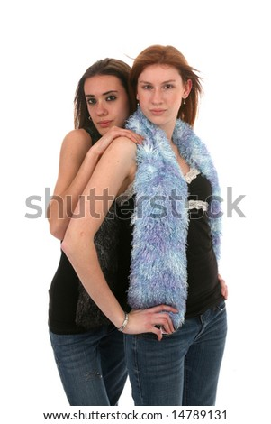two very thin teenage sisters standing close together and wearing black shirts and tight jeans - stock photo