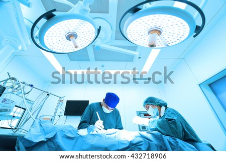 two veterinarian surgeons in operating room take with art lighting and blue filter - stock photo