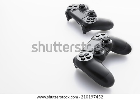 Two video game controllers - joysticks on white-gray background - stock photo