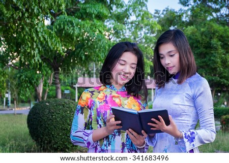 Two vietnamese girl read a book and happy , Vietnam traditional dress