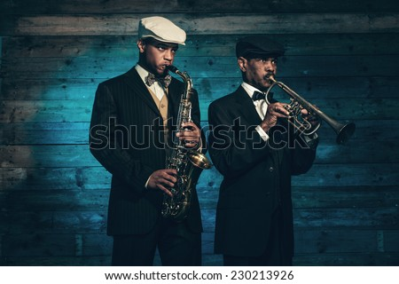 Two vintage african american jazz musicians with trumpet and saxophone in front of old wooden wall. Wearing black suit and cap. - stock photo