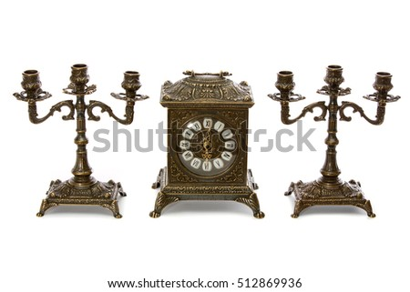 Two vintage bronze candle holder and clock on a white background